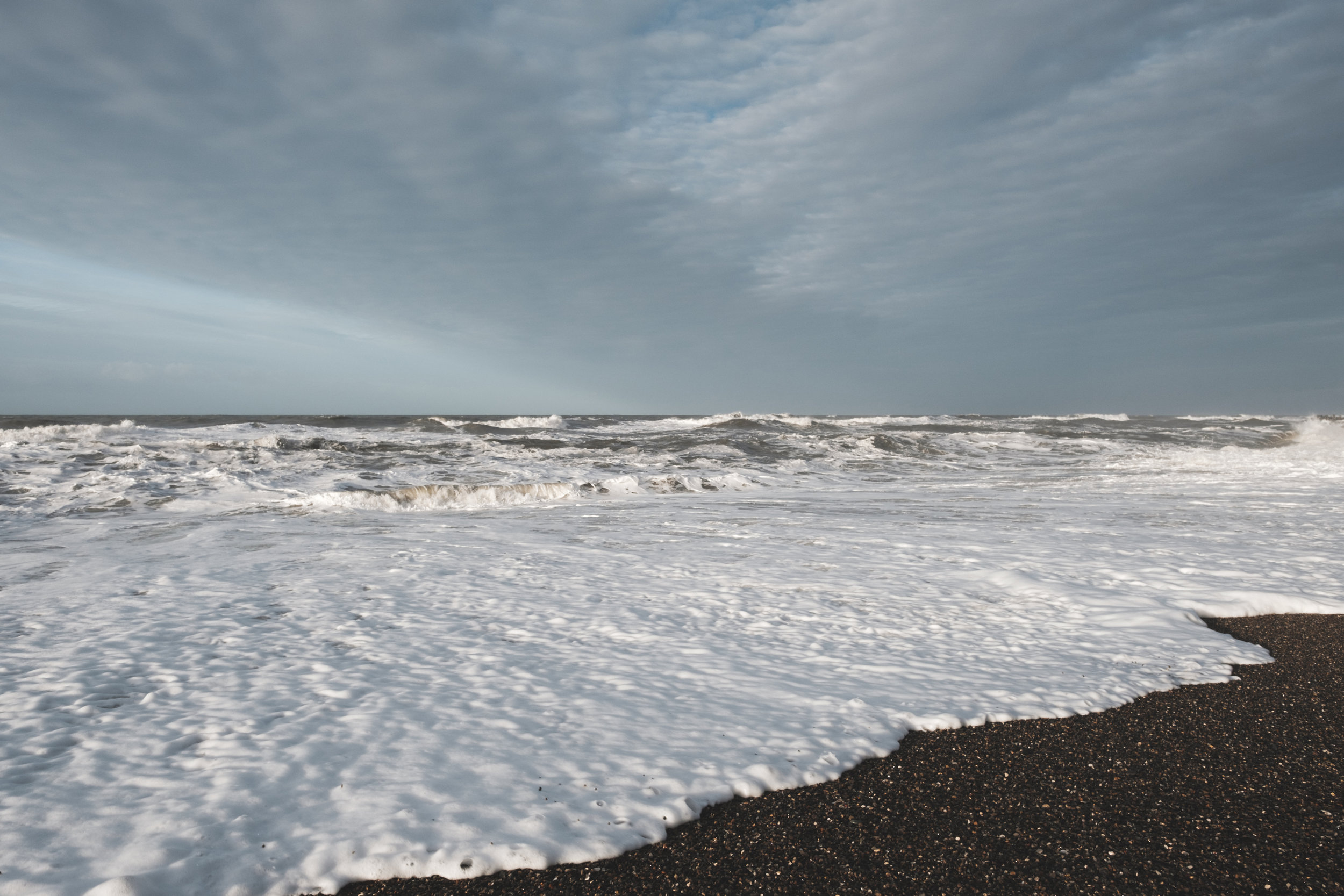 The sun brought out the colours of the sky, sea, foam as well as the darkness of the rocks.
