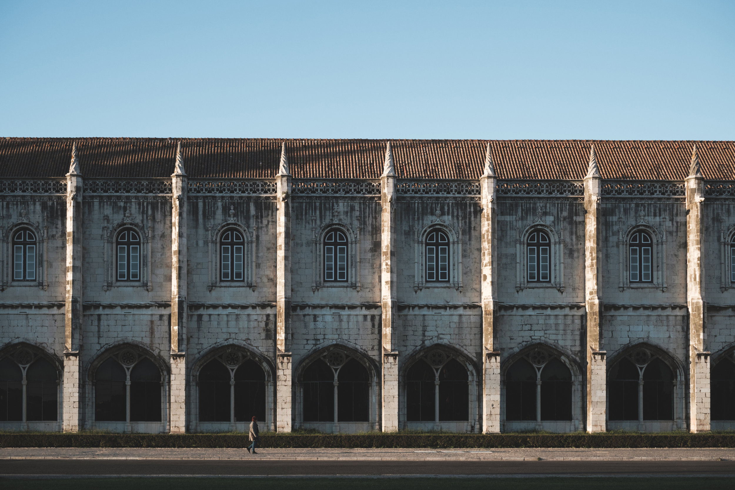 A man walks by the Jerónimos Monastery in Lisbon Portugal