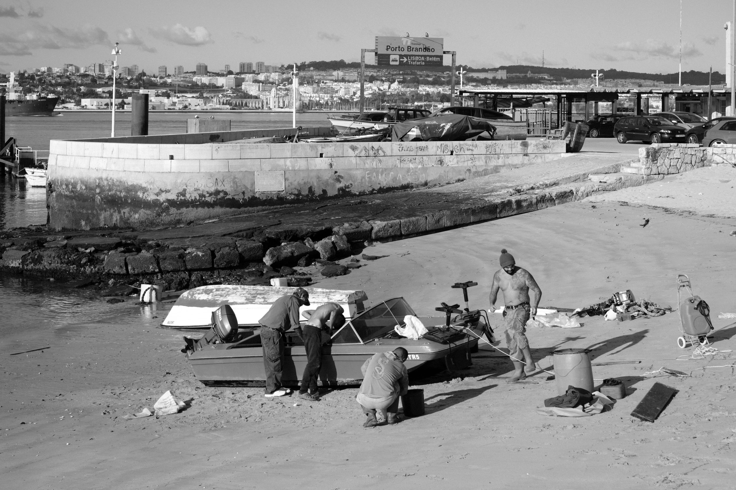 men are working around a small speedboat on a beach near the harbour in Lisbon Portugal