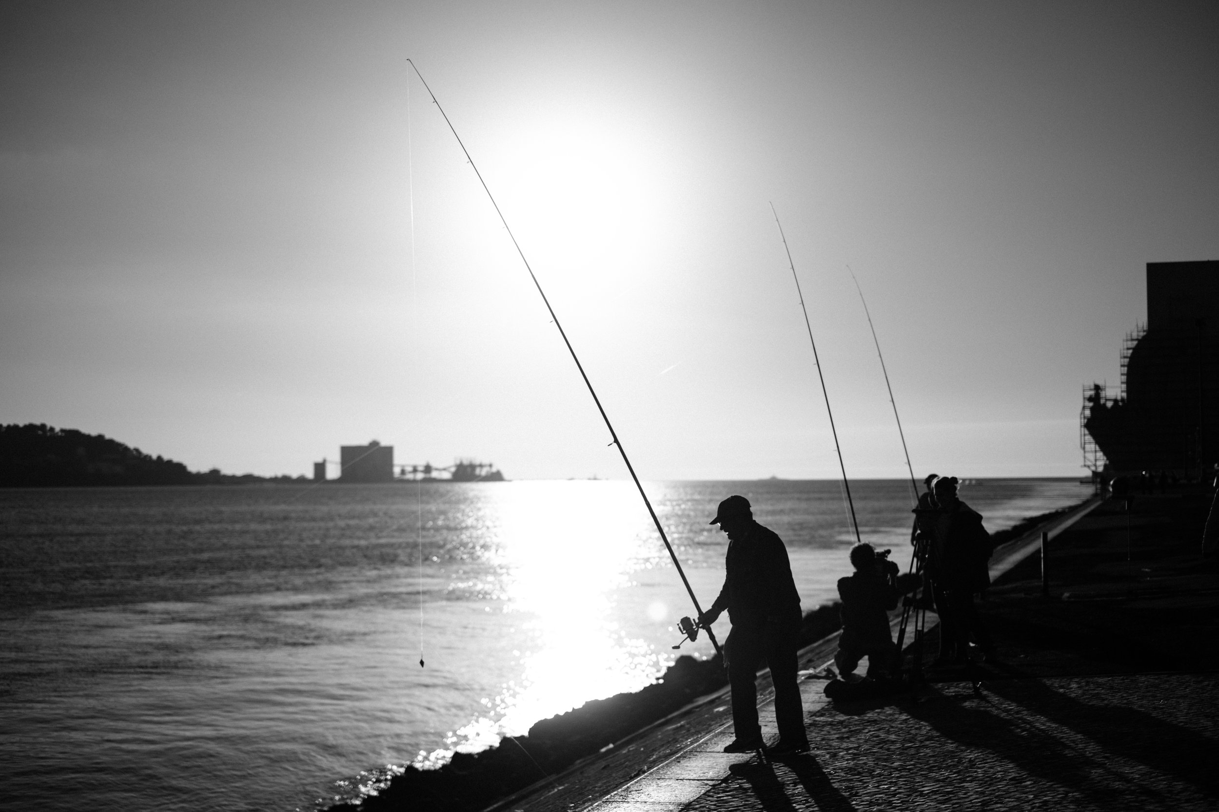 The men are fishing along the harbour in Lisbon enjoying the early December sun