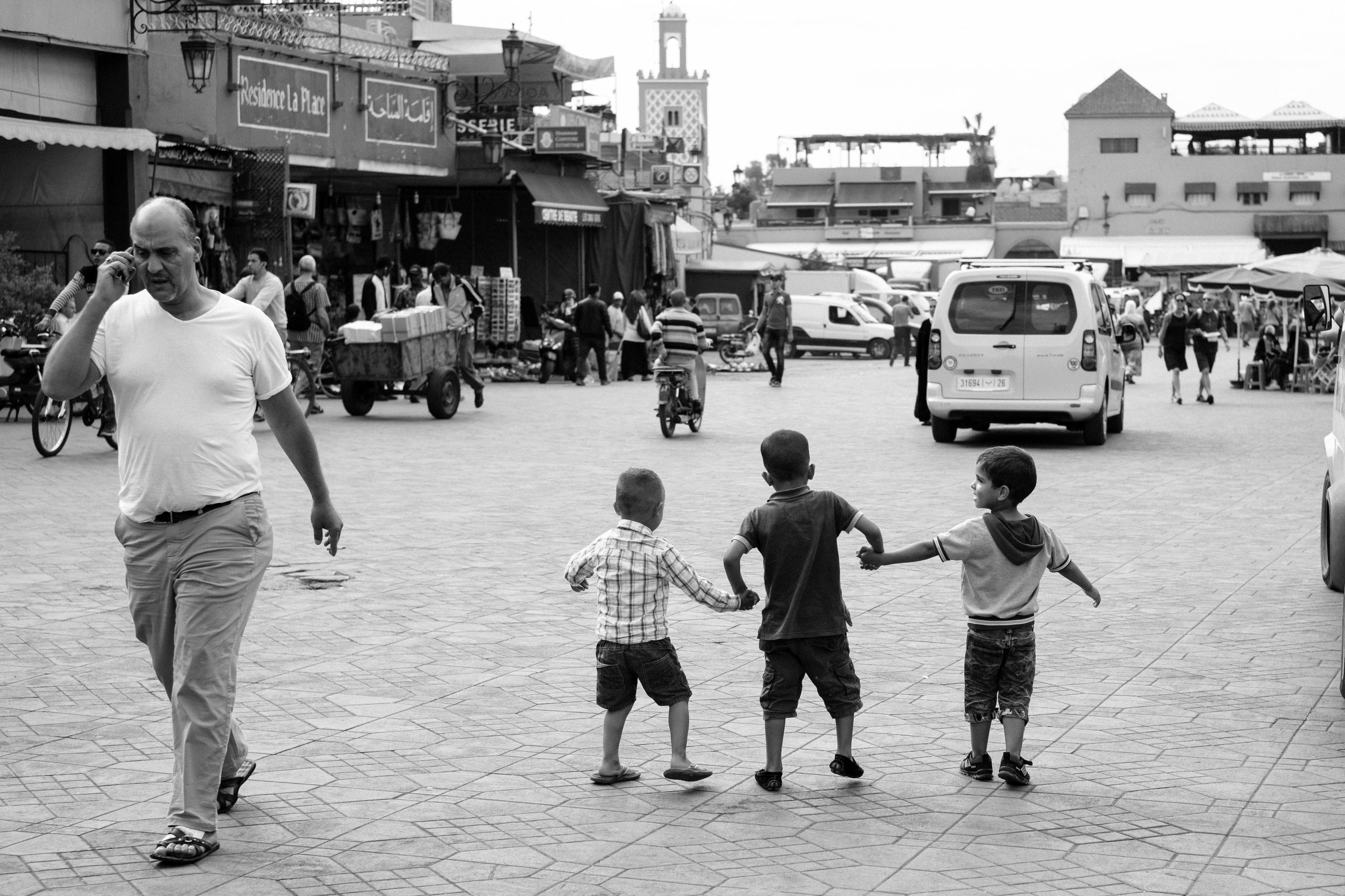 Three boys walk hand in hand while a man walks by on his mobile phone a the Jemaa el-Fna Square in the Medina District of Marrakech, Morocco