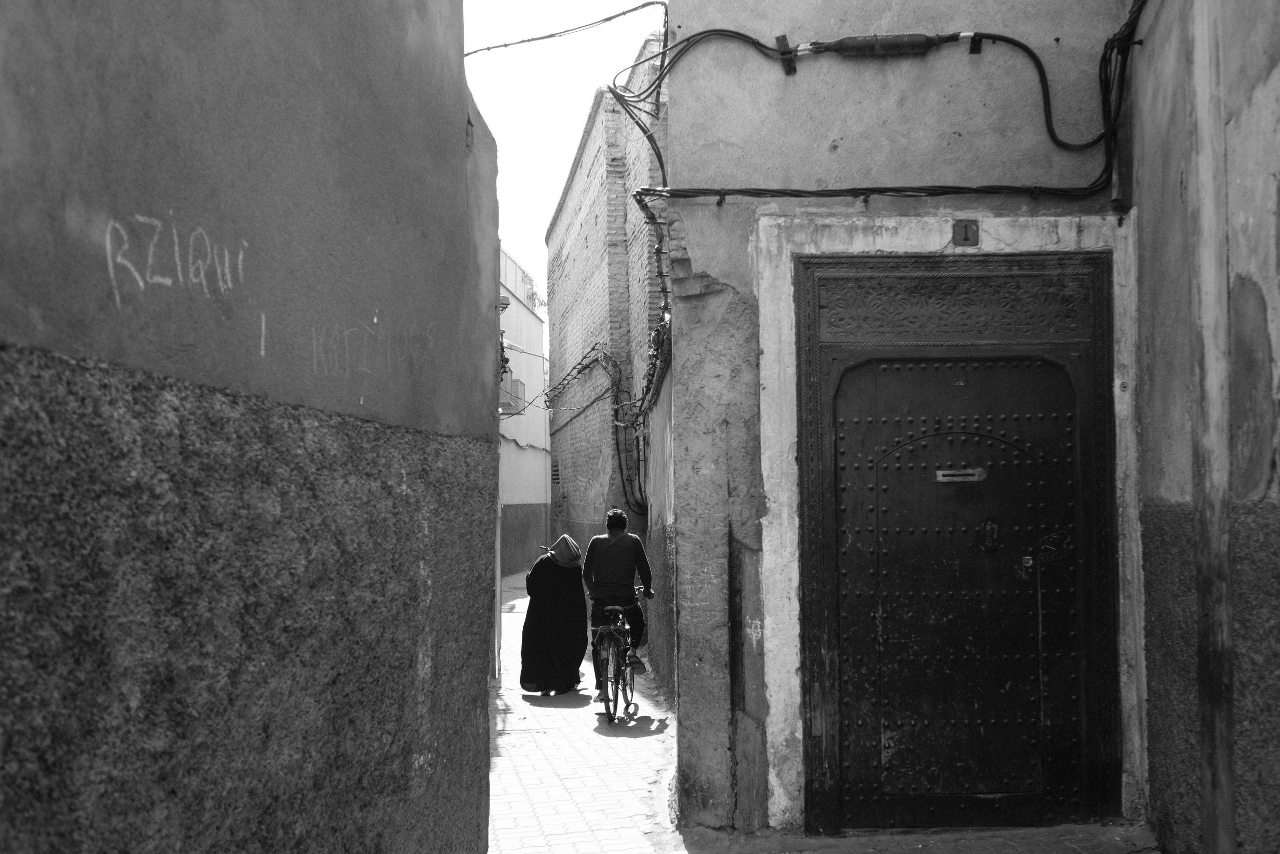 A woman carries goods and a man cycles through a narrow alley in the Medina District of Marrakech Morocco