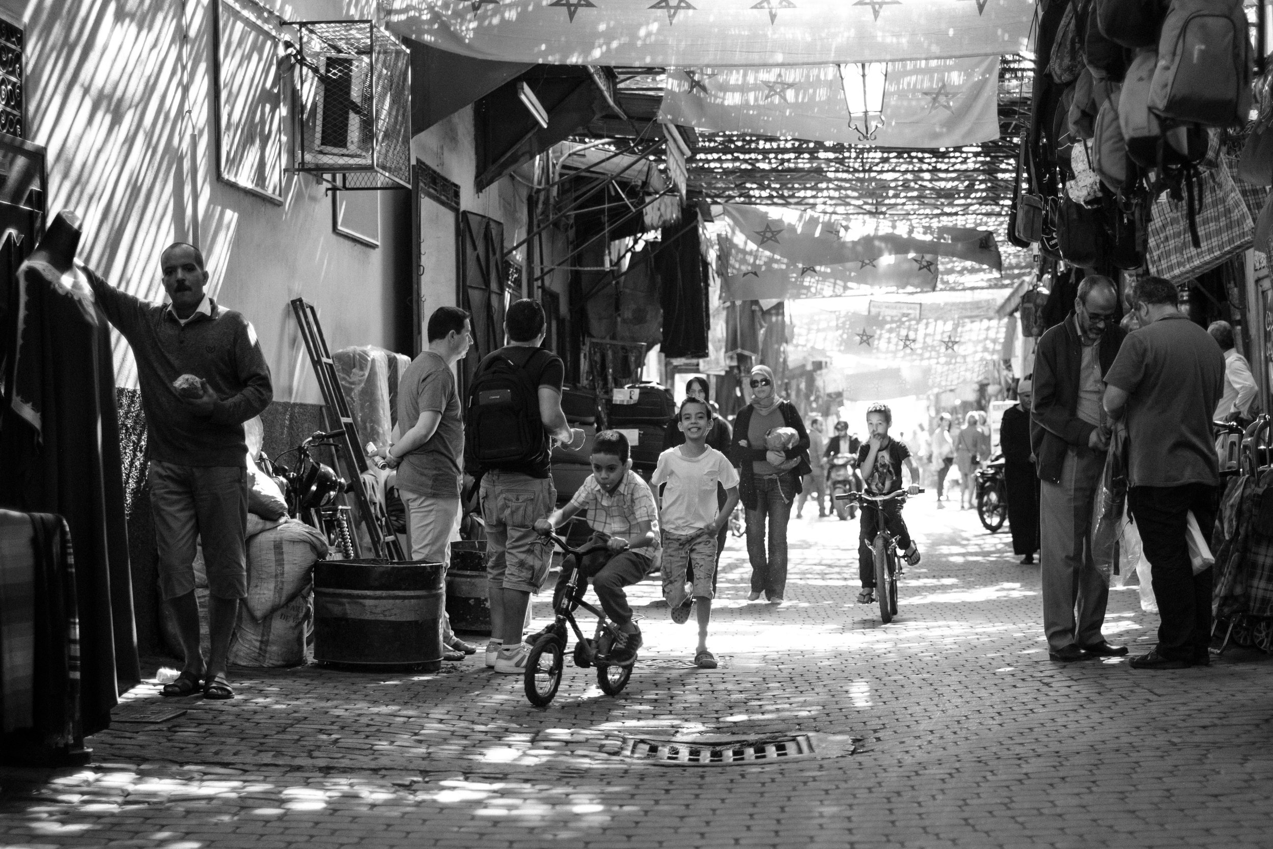 Boys are playing, running, cycling through the narrow streets in the Medina District of Marrakech Morocco