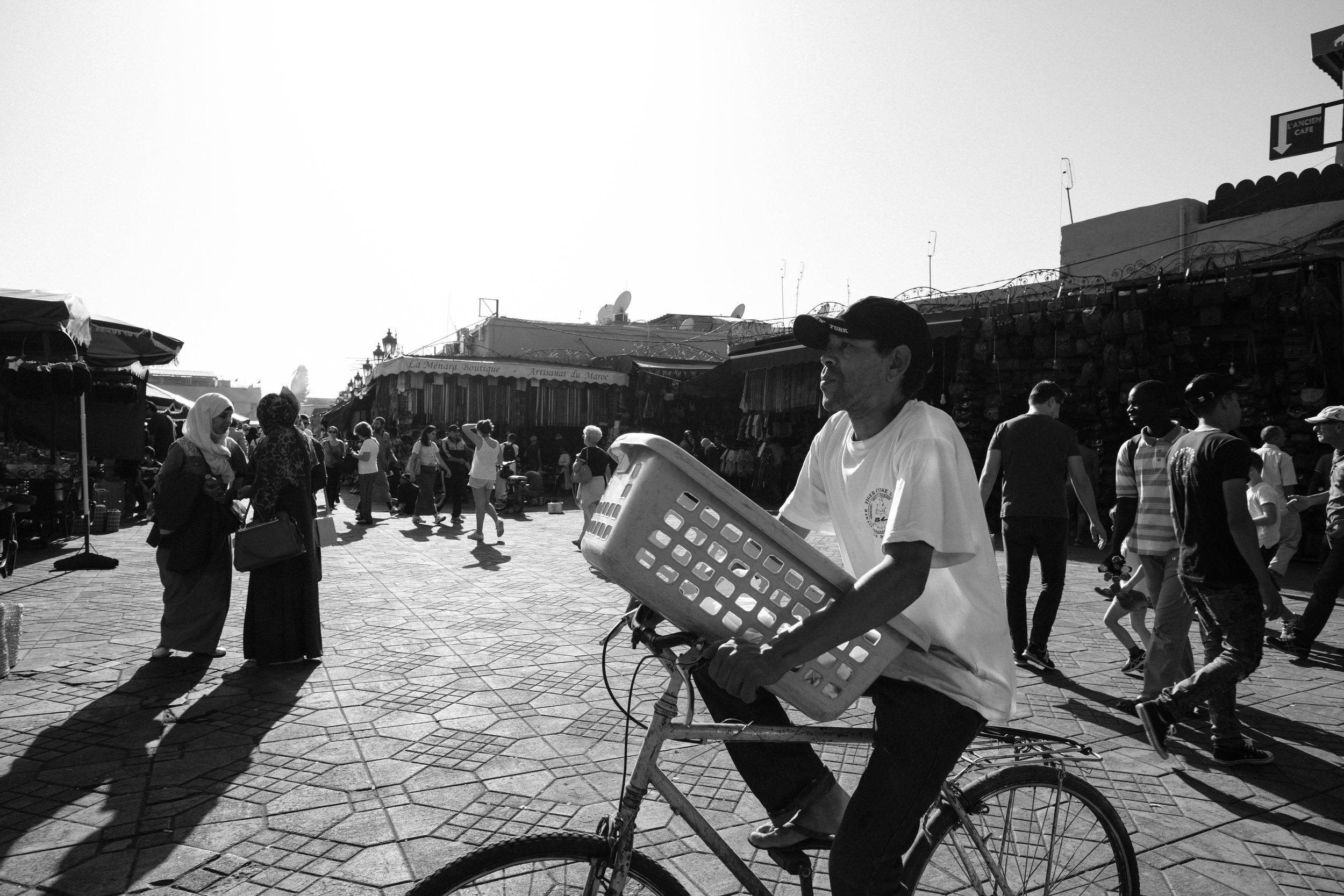 A man cycles at the main square market at Jemaa el-Fna Square in Marrakech Morocco