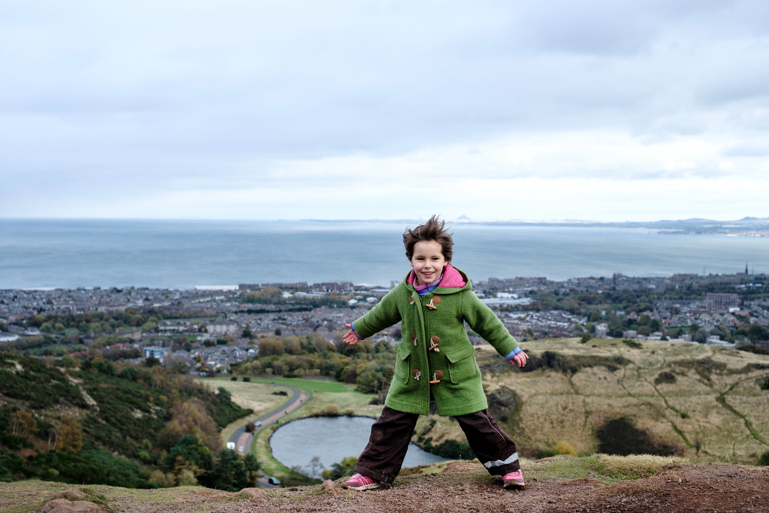 Naomin leans into the wind after hiking to the top of Arthur's Seat in Edinburgh