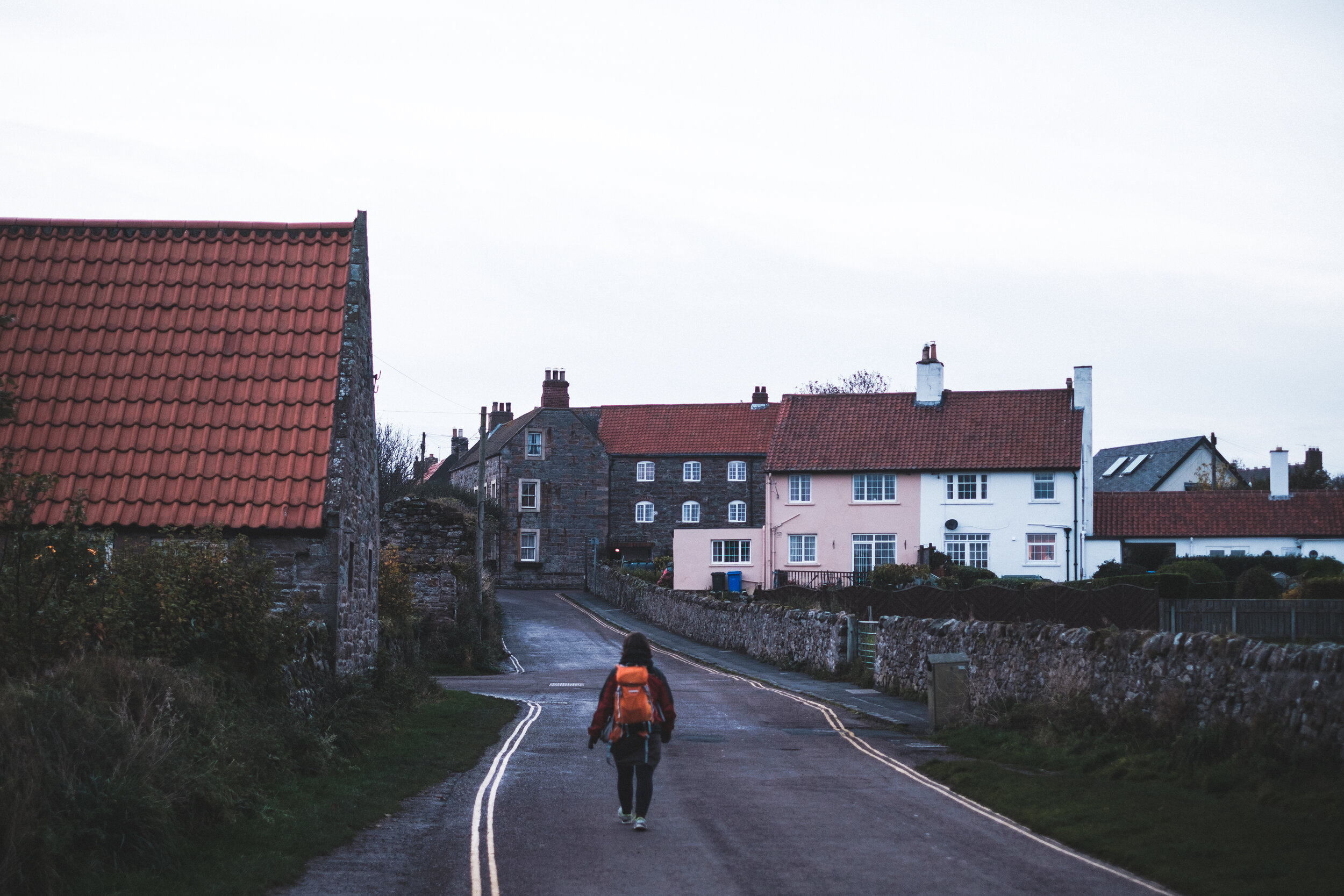 A woman walks down a quiet road at dusk on Holy Island in England