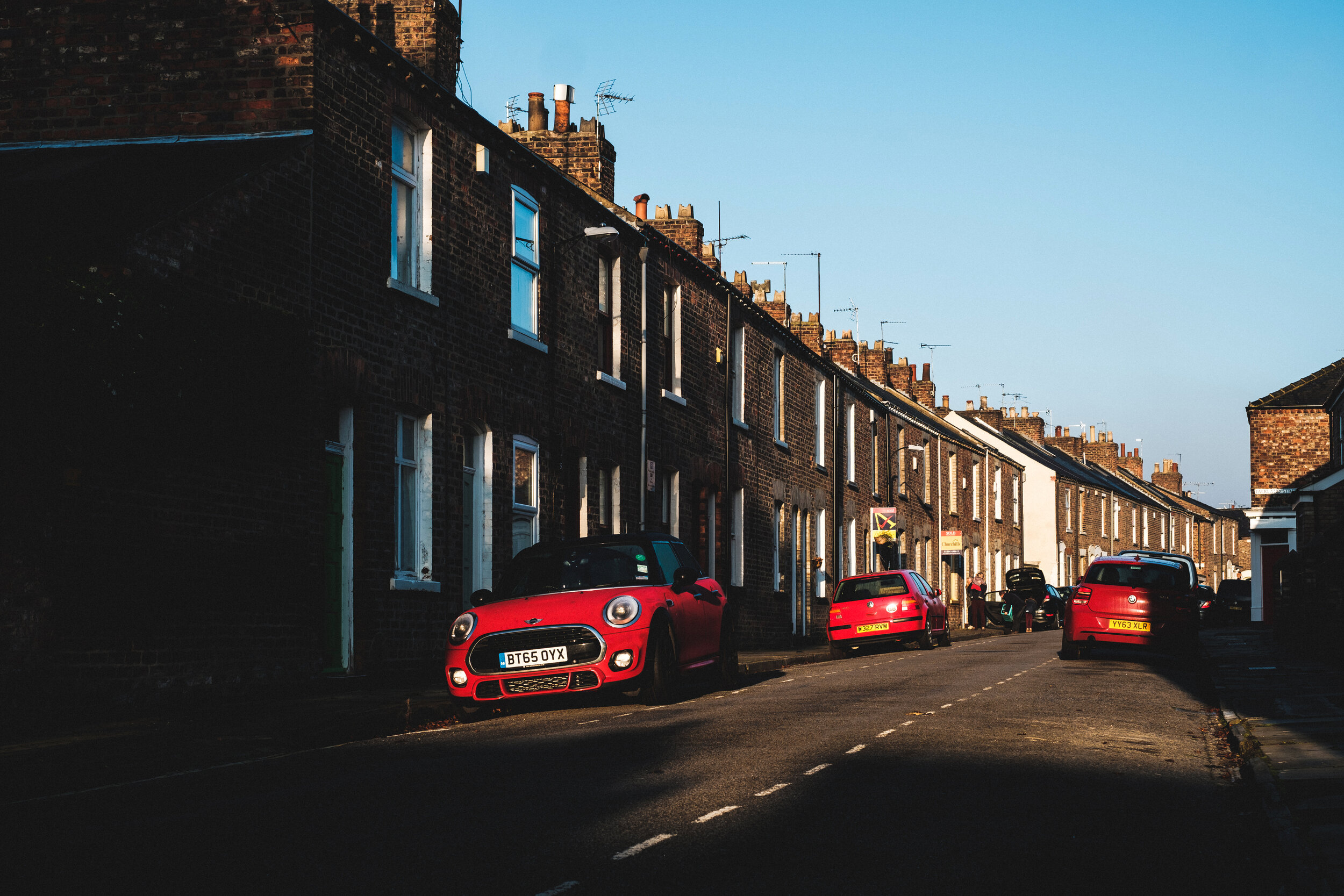 Three red cars parked in quiet street of York England