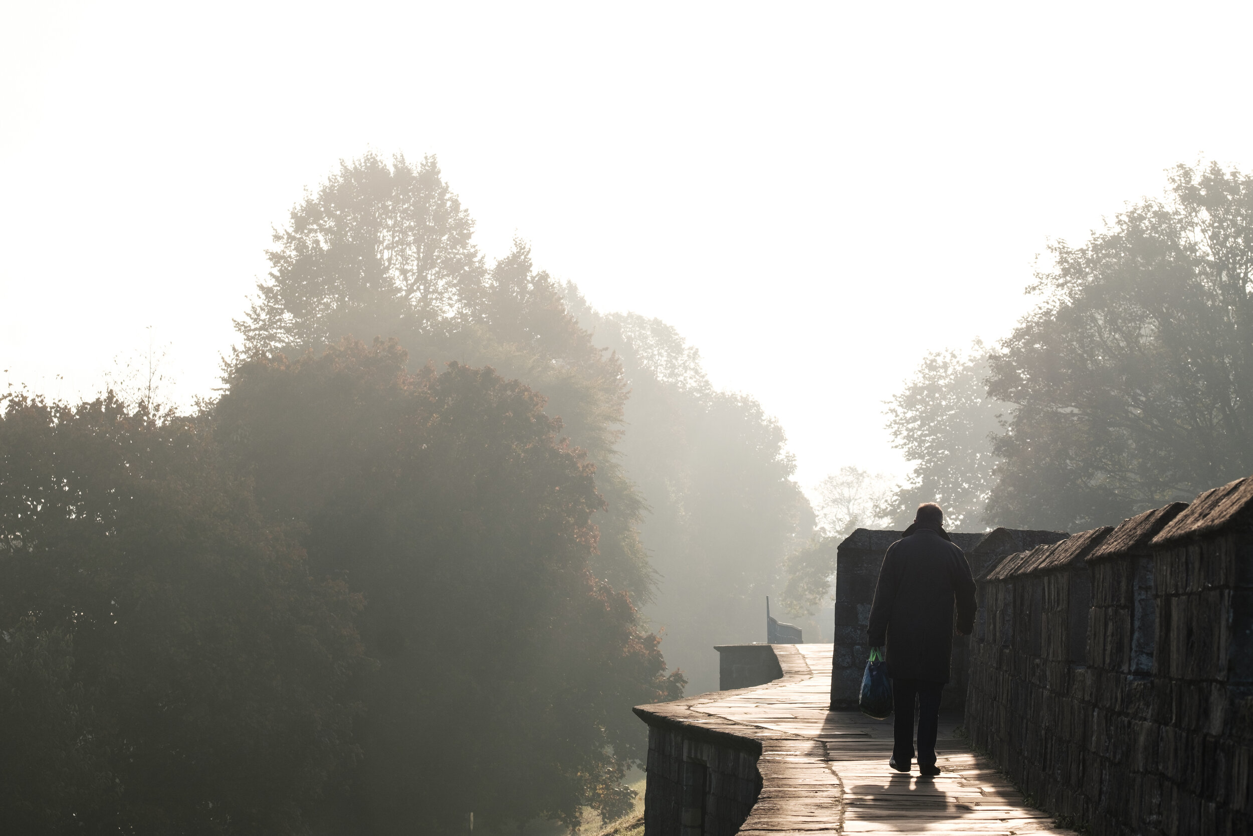 A man is out for an early fall morning walk at the historic walls of York in England
