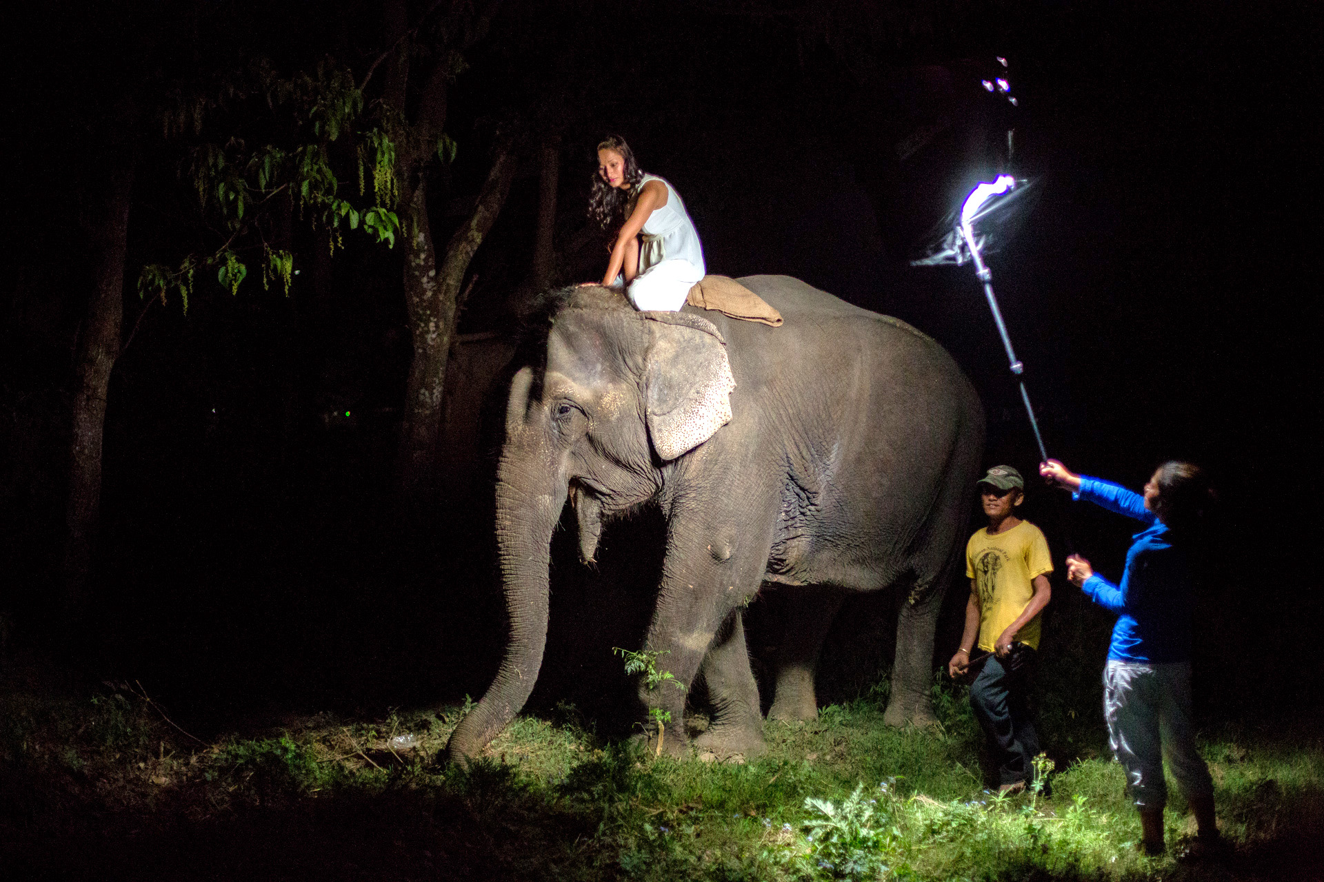 Behind the scenes of the shoot. Samjhana lighting the scene and our friend taking care of the Elephant.