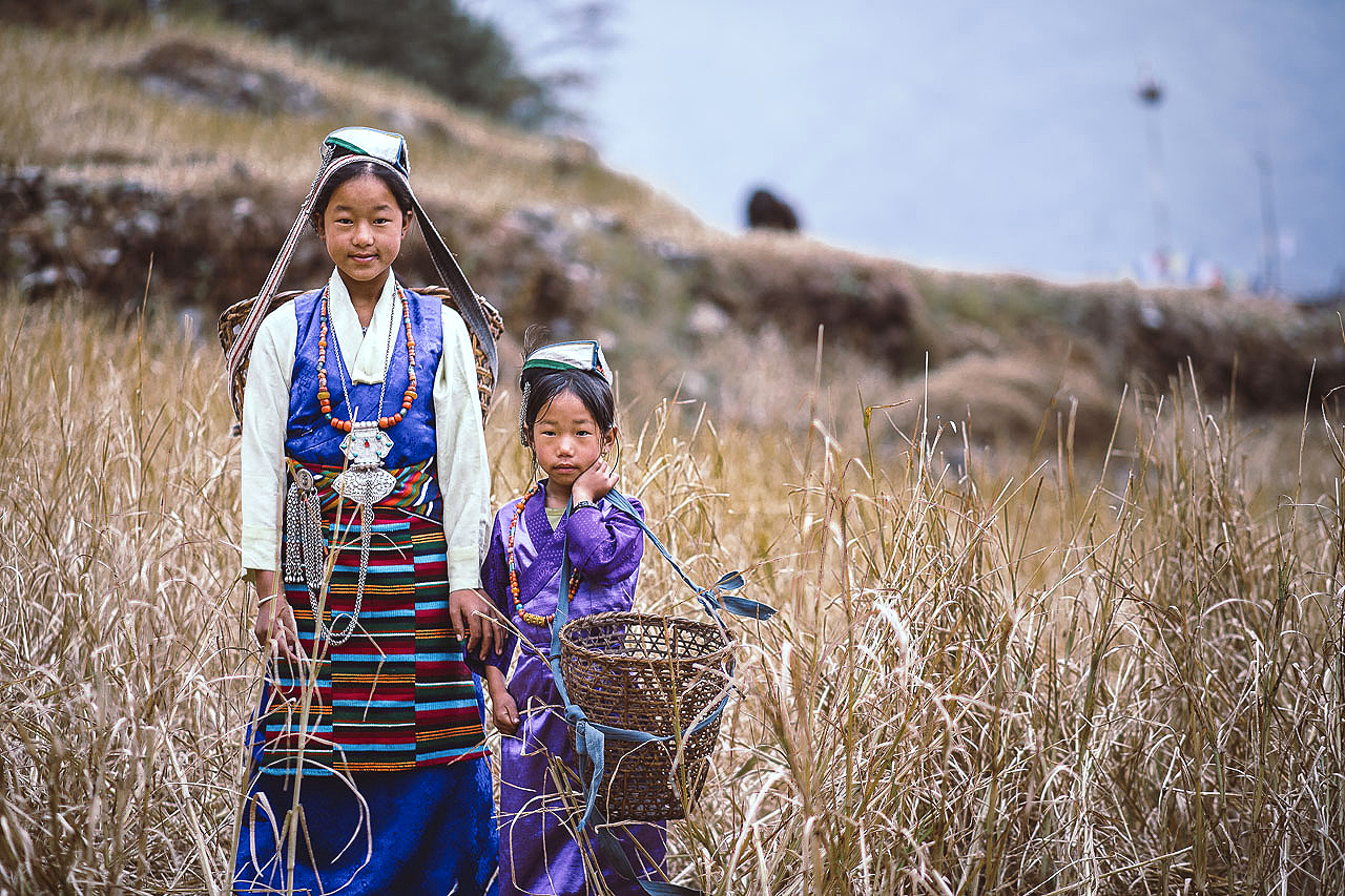 Sister posing in traditional Botia dresses in their families farming field.