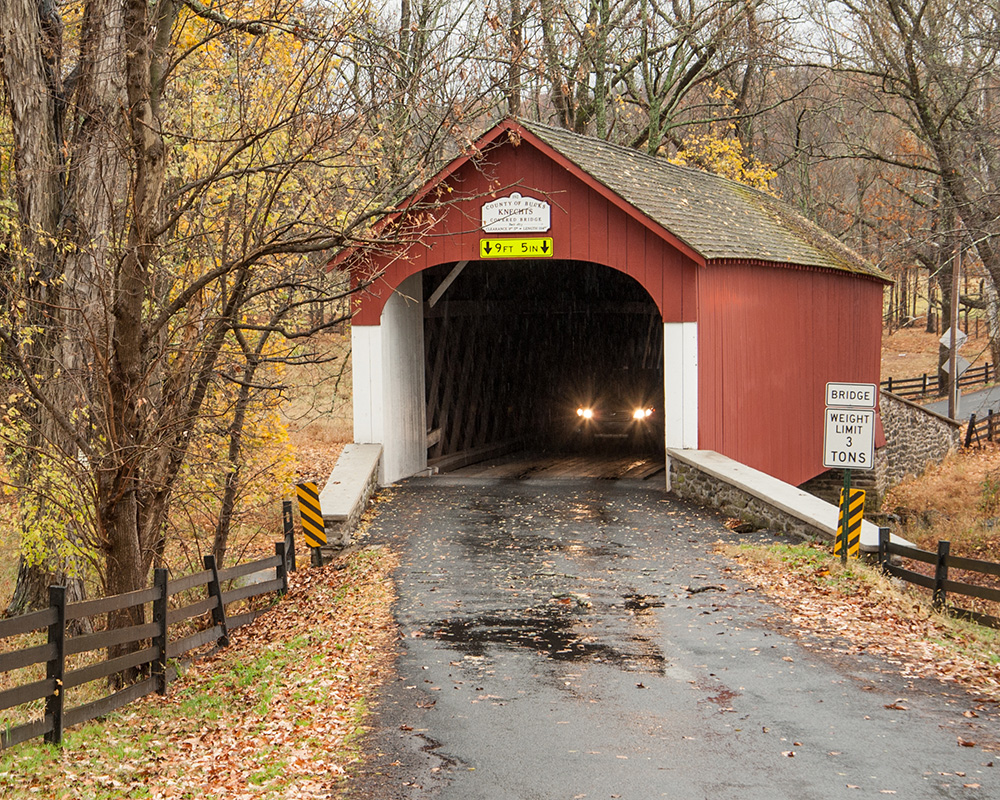 car emerges from covered bridge on rainy day