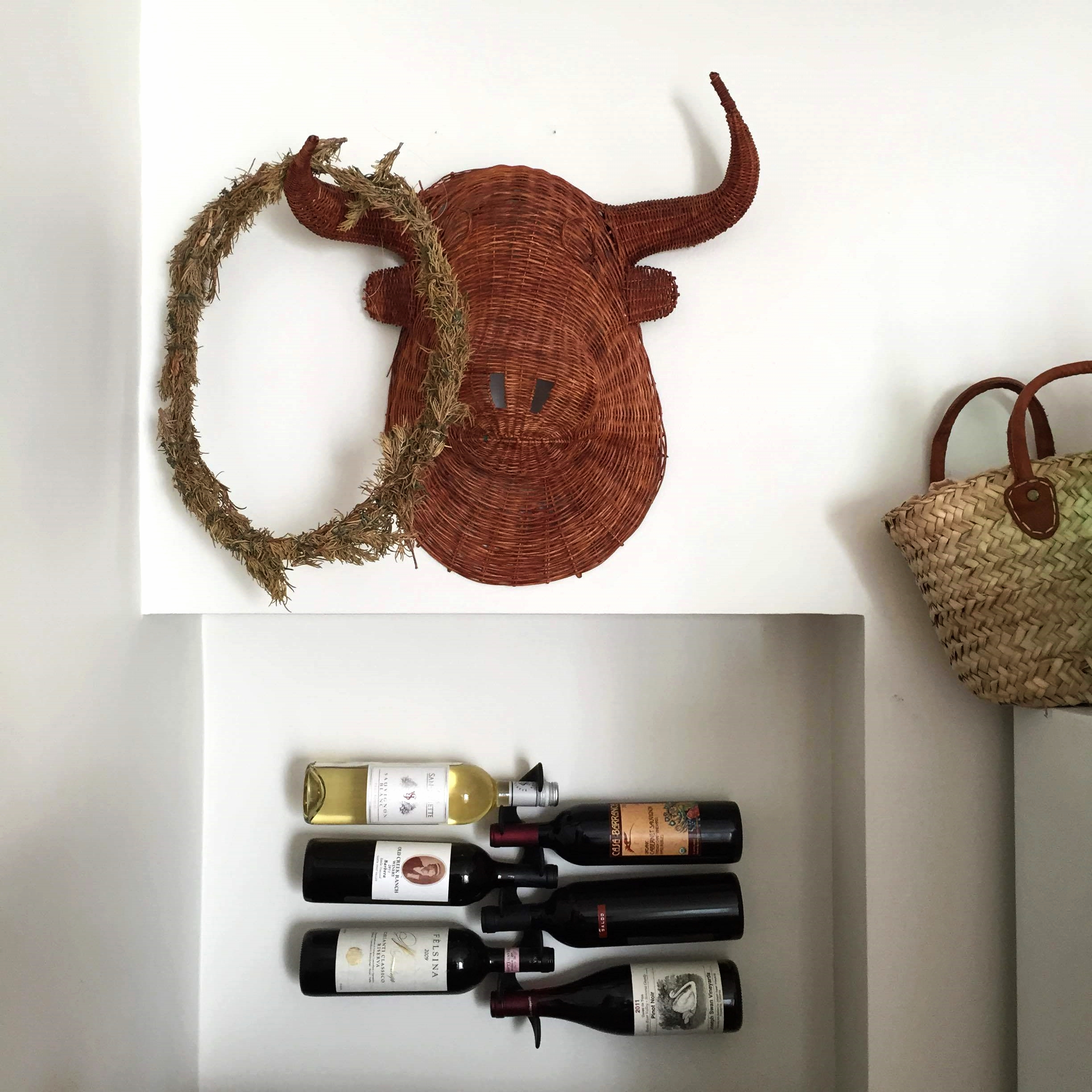 A favorite home accent: Our wicker bull's head. At some point, I decorated it with a dried rosemary wreath from our wedding and the look has stuck. The floating wine rack was a gift of mine to my husband. Continuing the woven theme, I have a weakness for straw baskets.