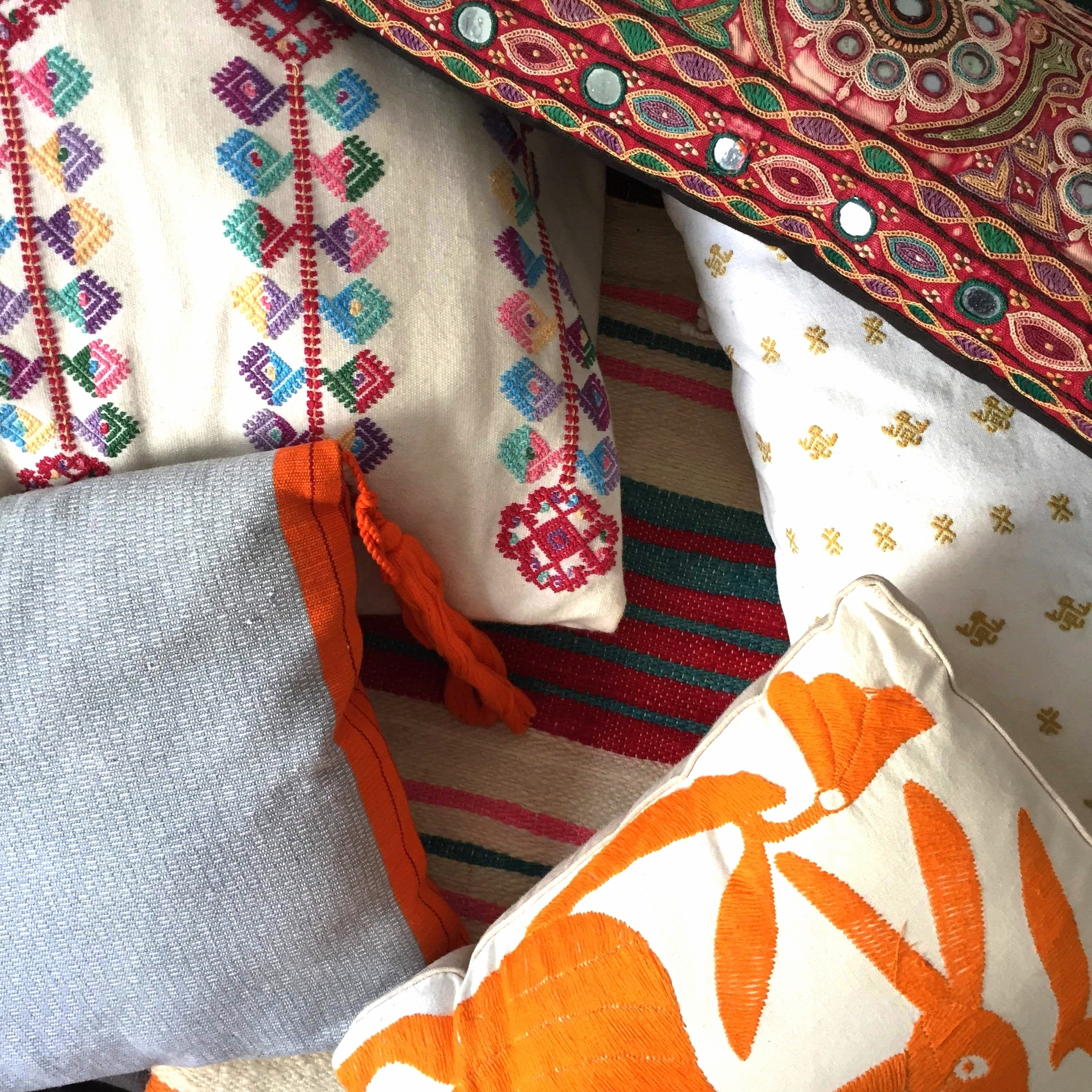 I keep my colorful pillows together in one room. This is my playful, sunny corner that is a definite break from the more muted color palette elsewhere. The pillows shown here are mostly from Mexico, with my mother's vintage Mexican blanket and bohemian pillow mixed in.