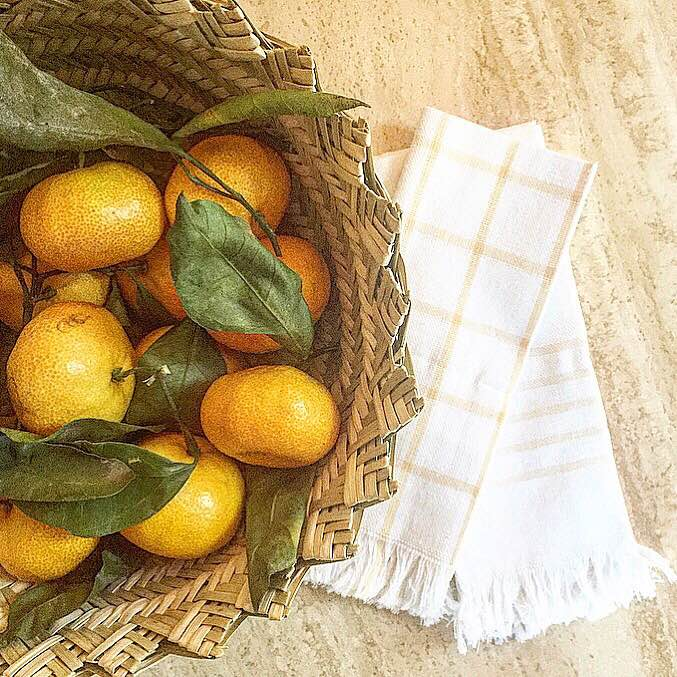 Tangerines are a favorite Thanksgiving day snack--and make for great table decor. Pictured here in a woven Mexican basket with Mexican napkins.