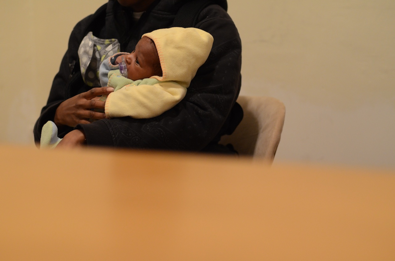 A participant holding her baby during an interview.