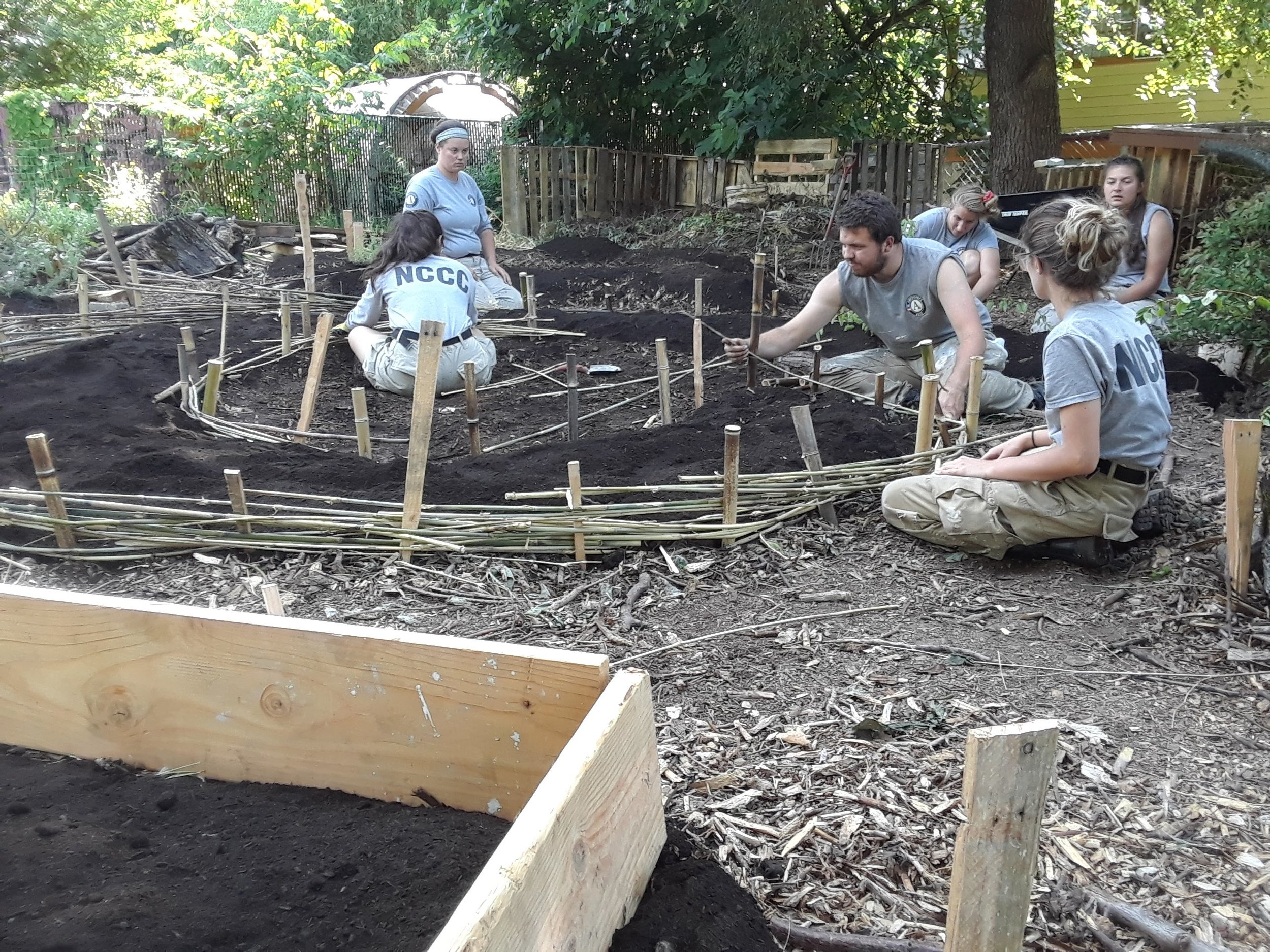 An AmeriCorps crew helps build an herb labyrinth.