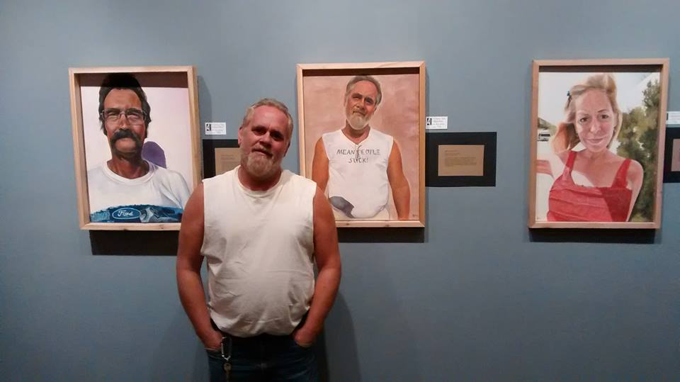 Bruce McCoy posing next to his painting, America the Working Poor, Portrait of Bruce (AKA Bar Creep), 2014.