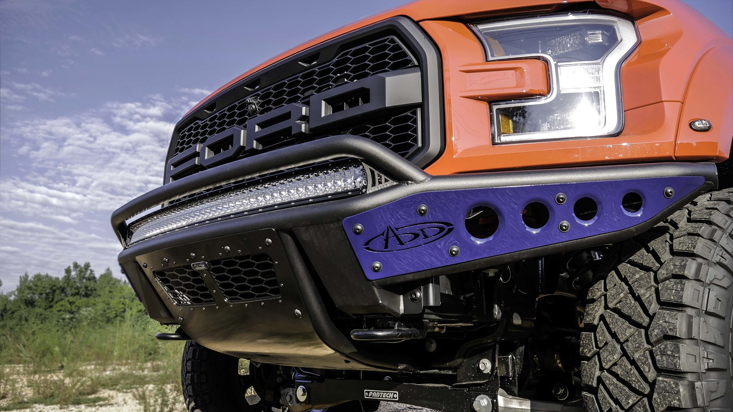Ford Raptor Lifted Red with Blue Bumper.jpg