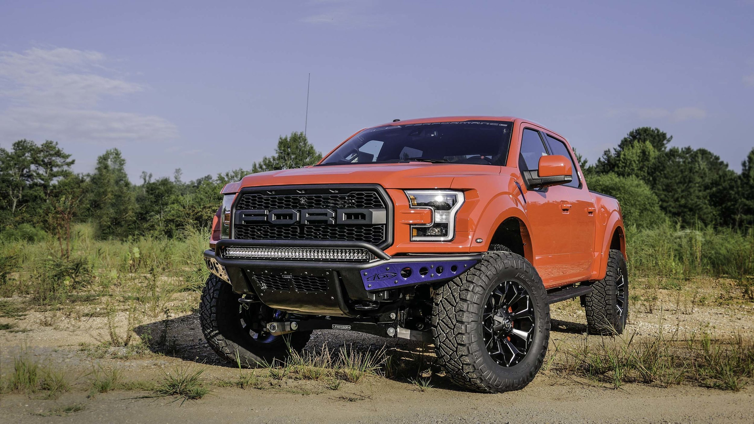 Ford Raptor Lifted Red with Blue Bumper Front Qtr.jpg