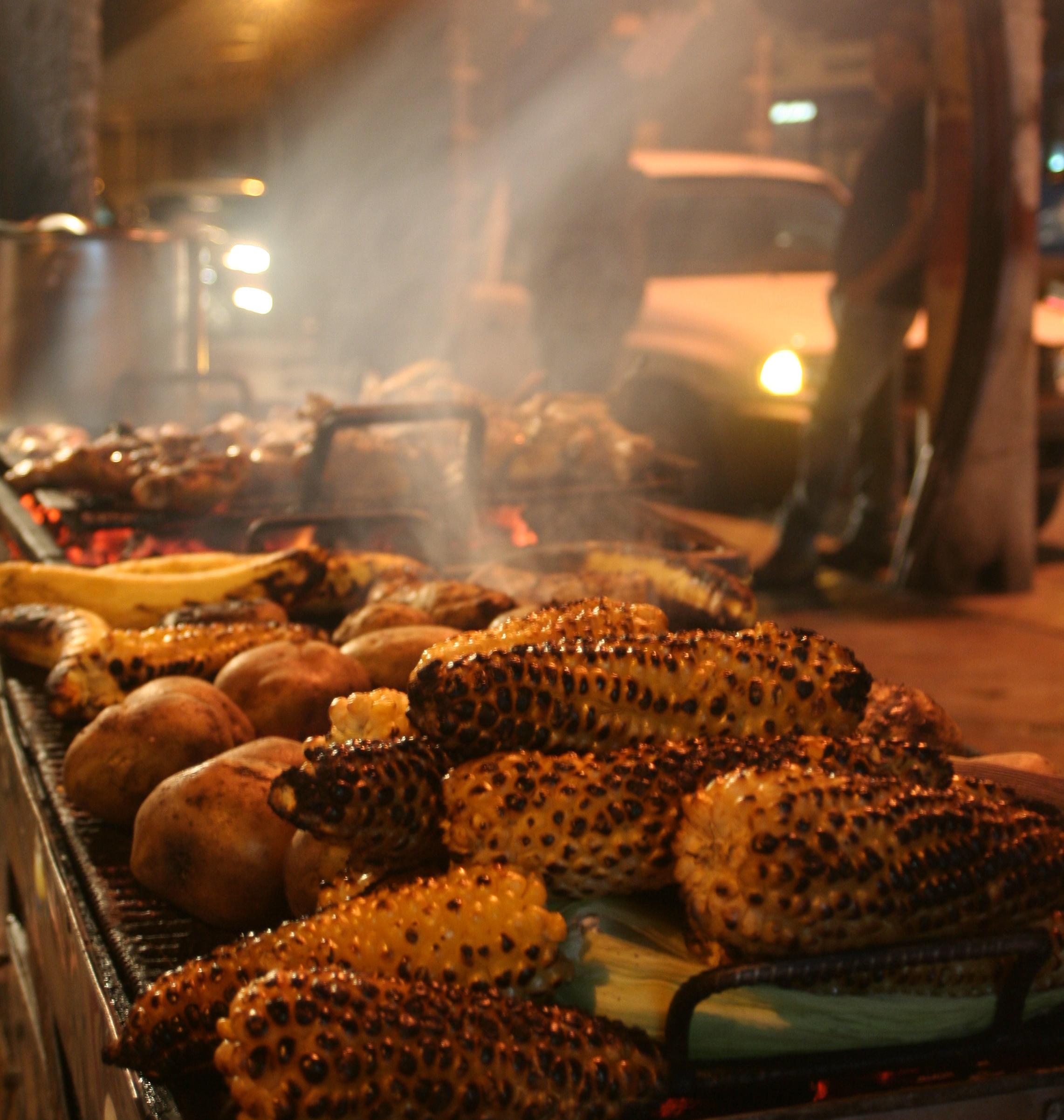 Batatas, majs och lökar på en gatugrill i Ecuador.