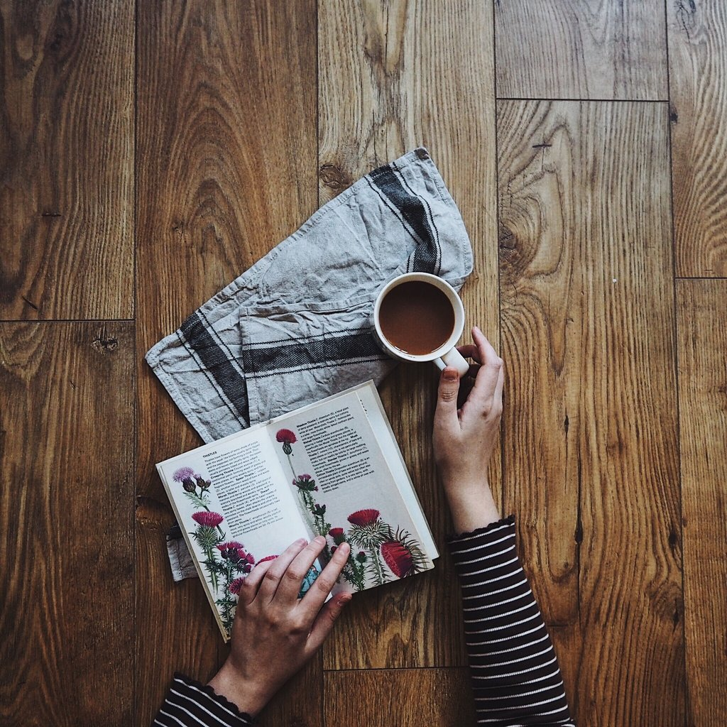 Hands drinking tea and reading wildflower book on wooden table.jpg