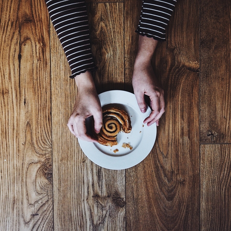 Hands holding a cinnamon whirl on a wooden table.jpg