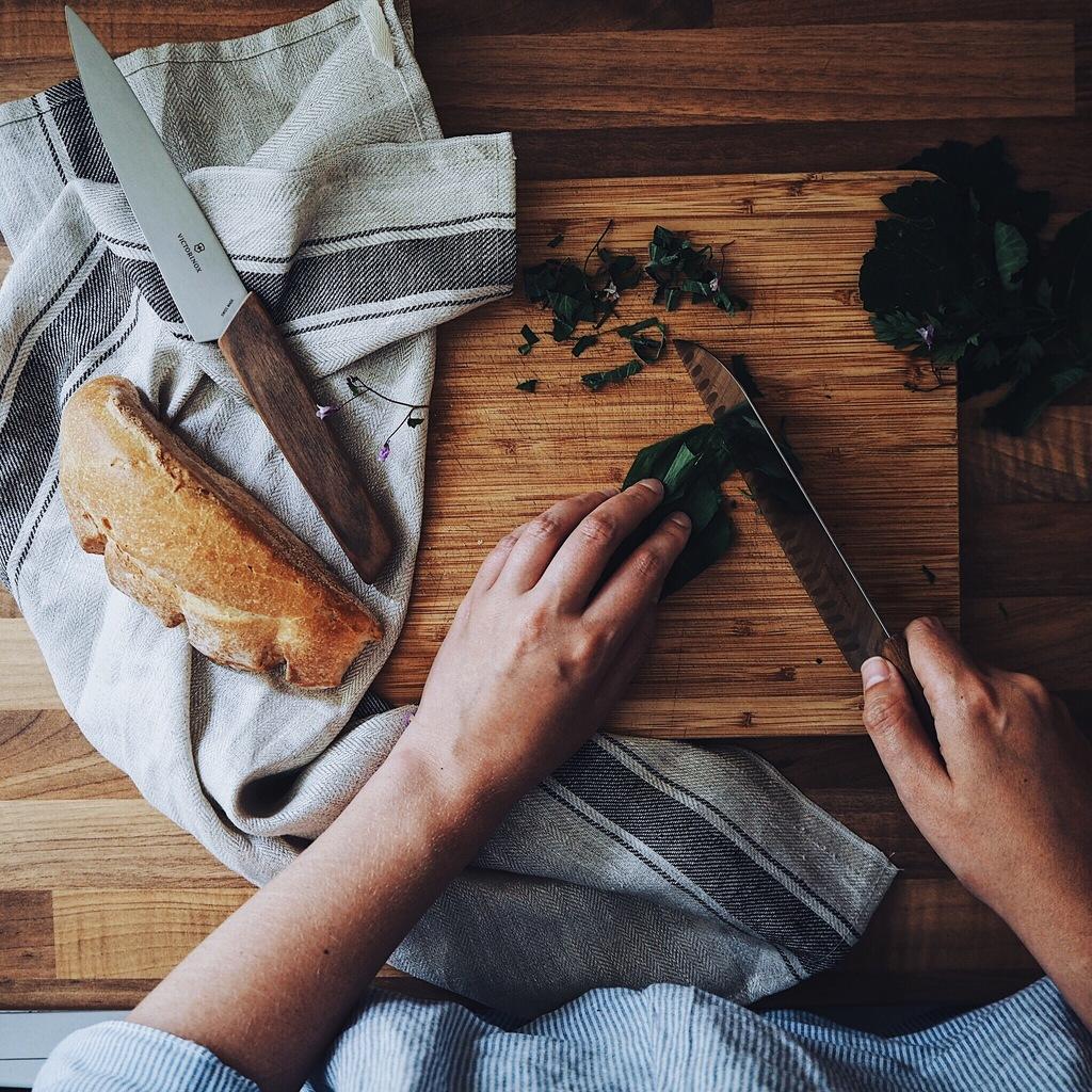 Girl chopping wild garlic on a wooden surface.jpg