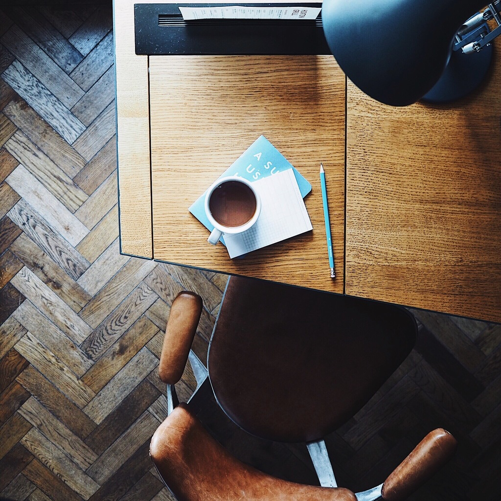 Cup of tea on a notebook on the corner of a mid-century desk with a leather chair.jpg