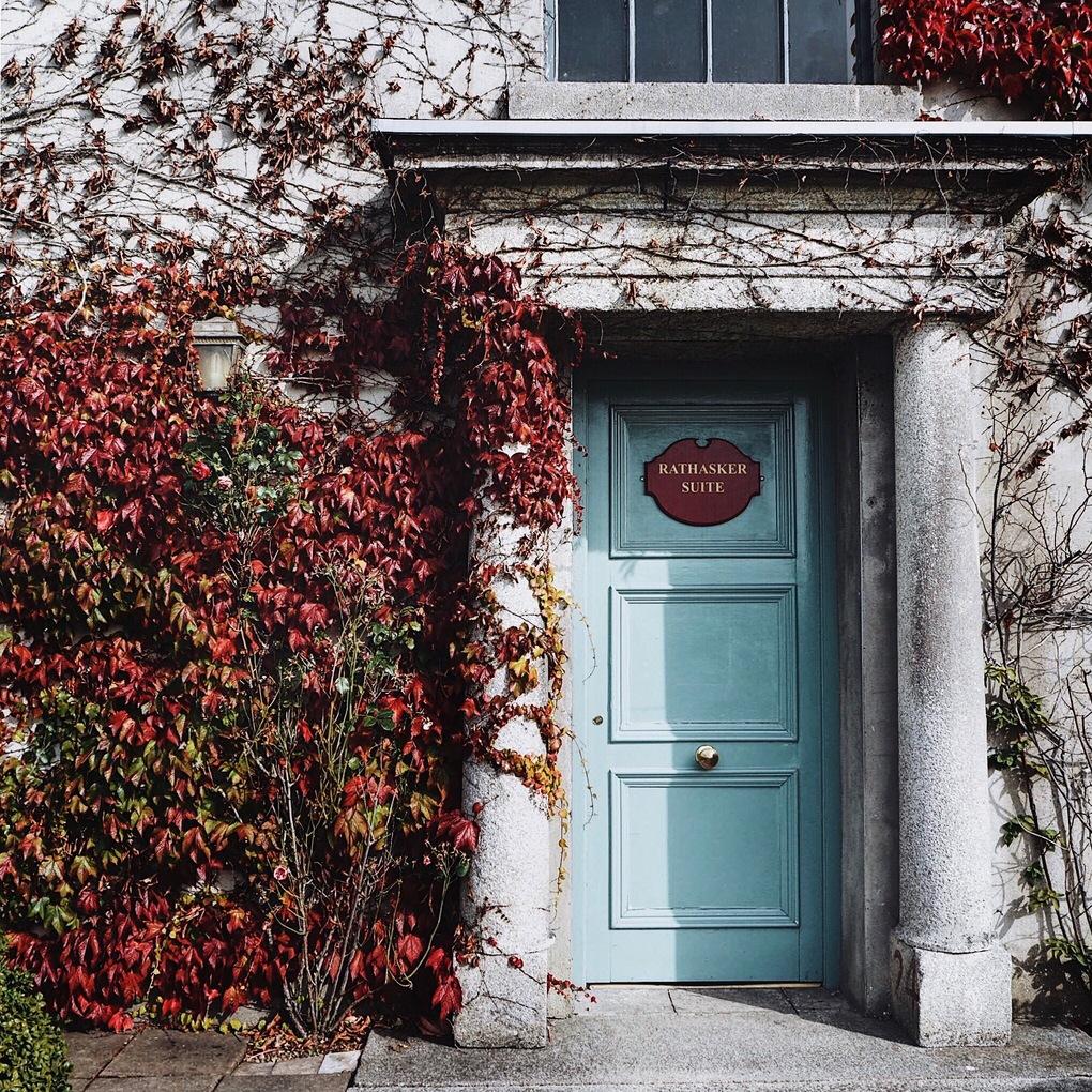 Light blue door with red Virgina Creeper across the walls.jpg