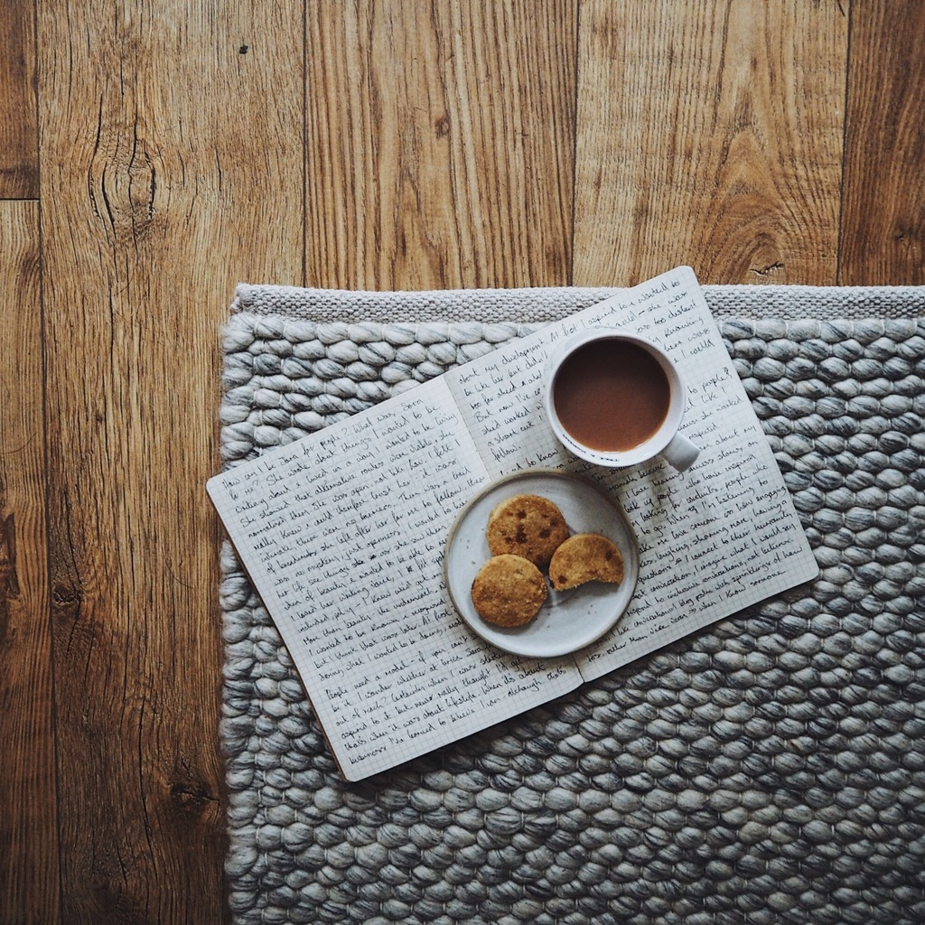 Tea and biscuits on an open book on a grey wool rug.jpg