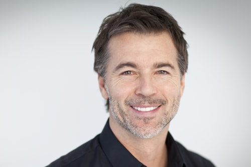 a middle aged man smiling with a full set of veneers