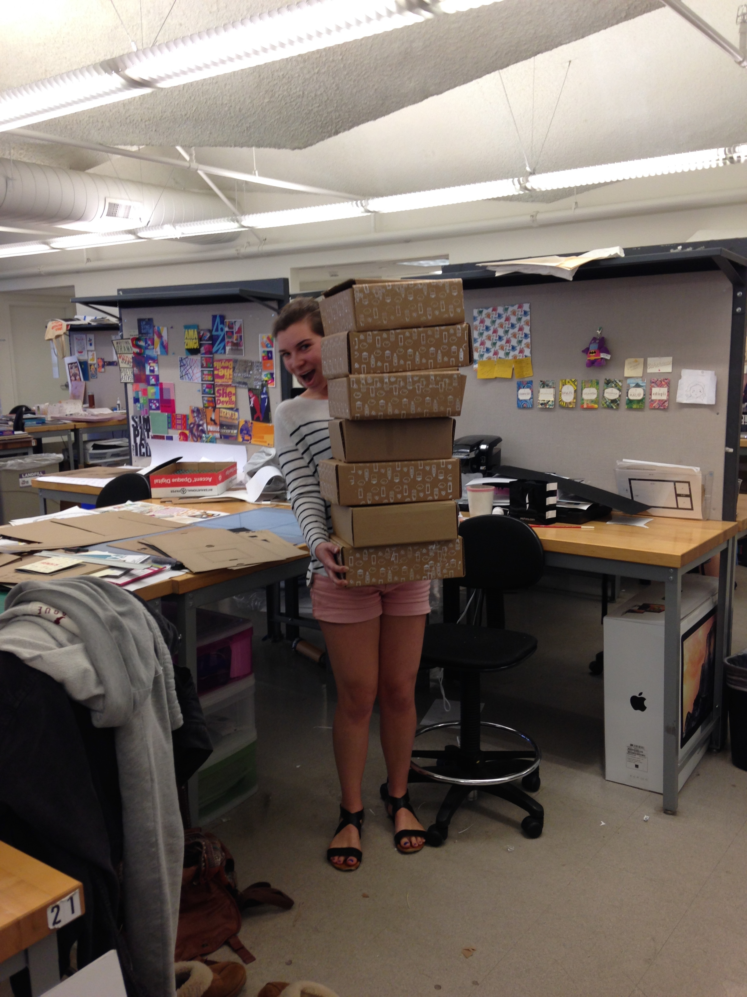 Me, with just a few of the iterations of boxes that I cut, put together, and screen printed myself.