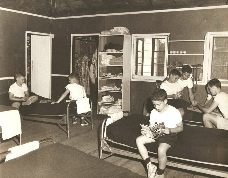 """Vintage 1950s Bunk Scene:  Maybe staged just a little bit for the camera? The boy in the foreground is reading """"The Wailing Siren Mystery,"""" a Hardy Boys adventure first published in 1951. Current campers should notice: the towel folded on the end of each bed; the wood door to the bathroom, metal army cots (very tough on knees when you caught a corner); windows on the other side of the screens that open out rather than up and down; no comforters in sight (only wool blankets); and a basically empty shelf over the bed (except for 5 tennis balls, a mitt, and a metal canteen)."""
