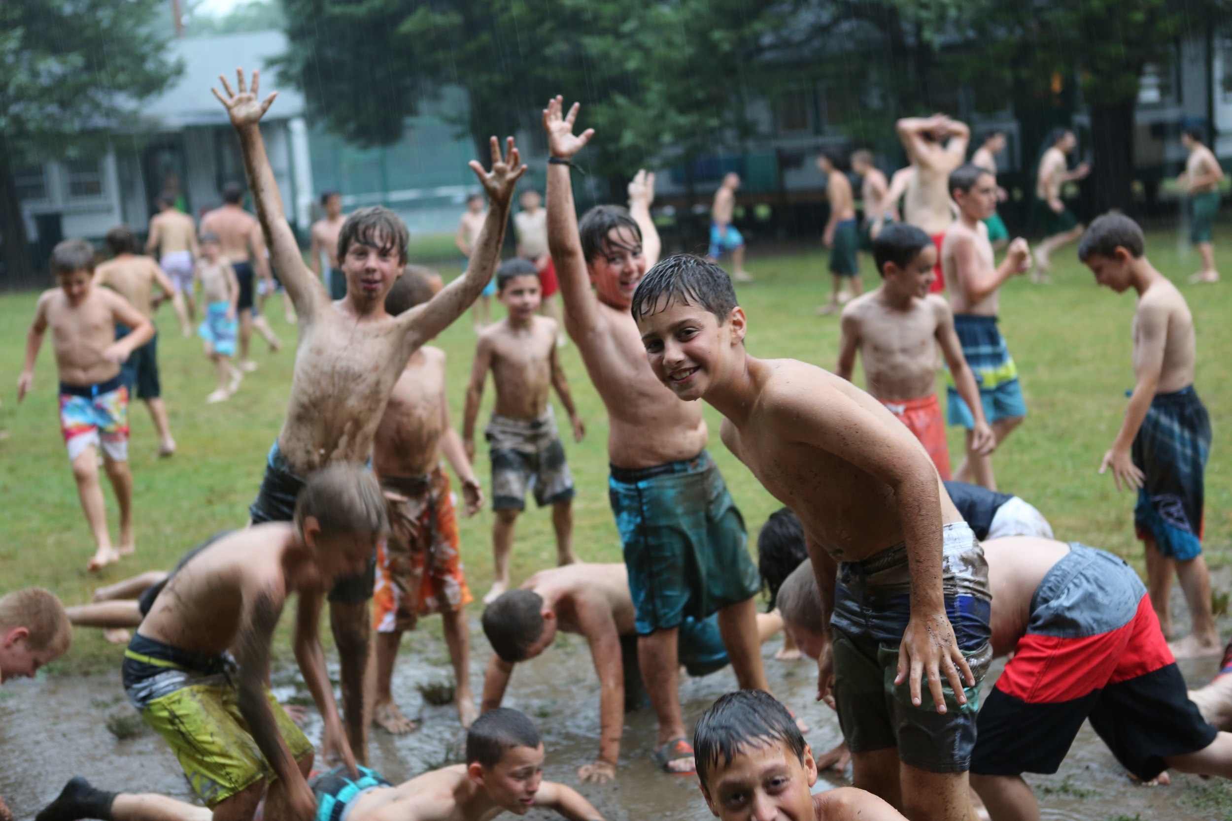 A little rain doesn't get us down! Boys side enjoys a mud sliding session during some summer showers...