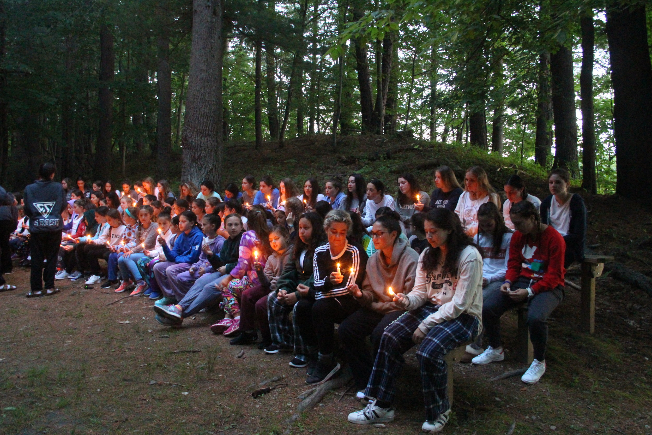 Campers of all ages light a candle during the campfire to make a wish.