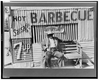 Man of color sitting on bench at side of barbecue stand made of galvanized metal, Corpus Christi, Tx, Library of Congress, Prints and Photographs Div LC-USF33- 012032-M2