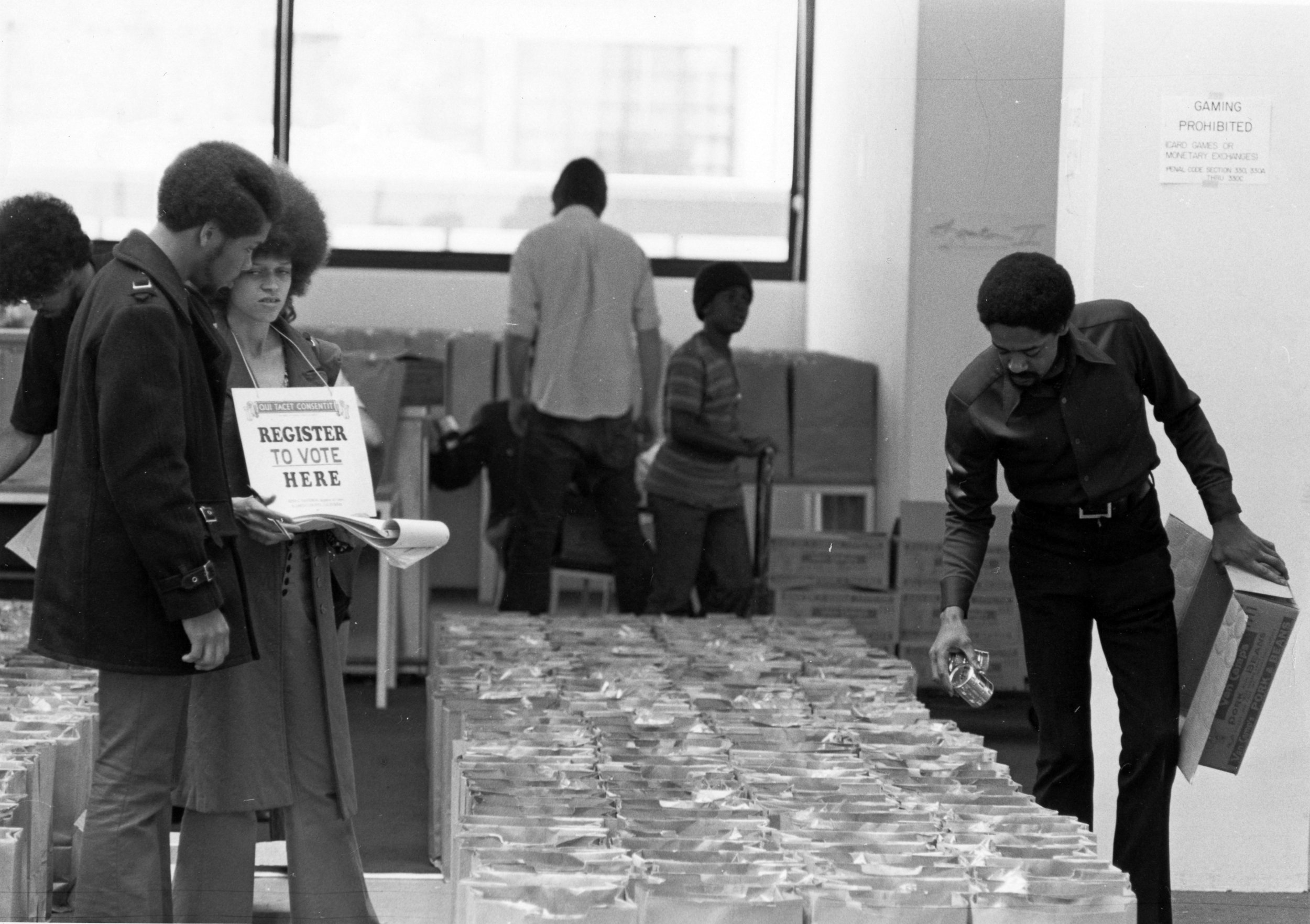 Voter registration volunteers left and Bobby Seale right loading grocery bags in 1972, Courtesy of the Stanford University Special Collections Library