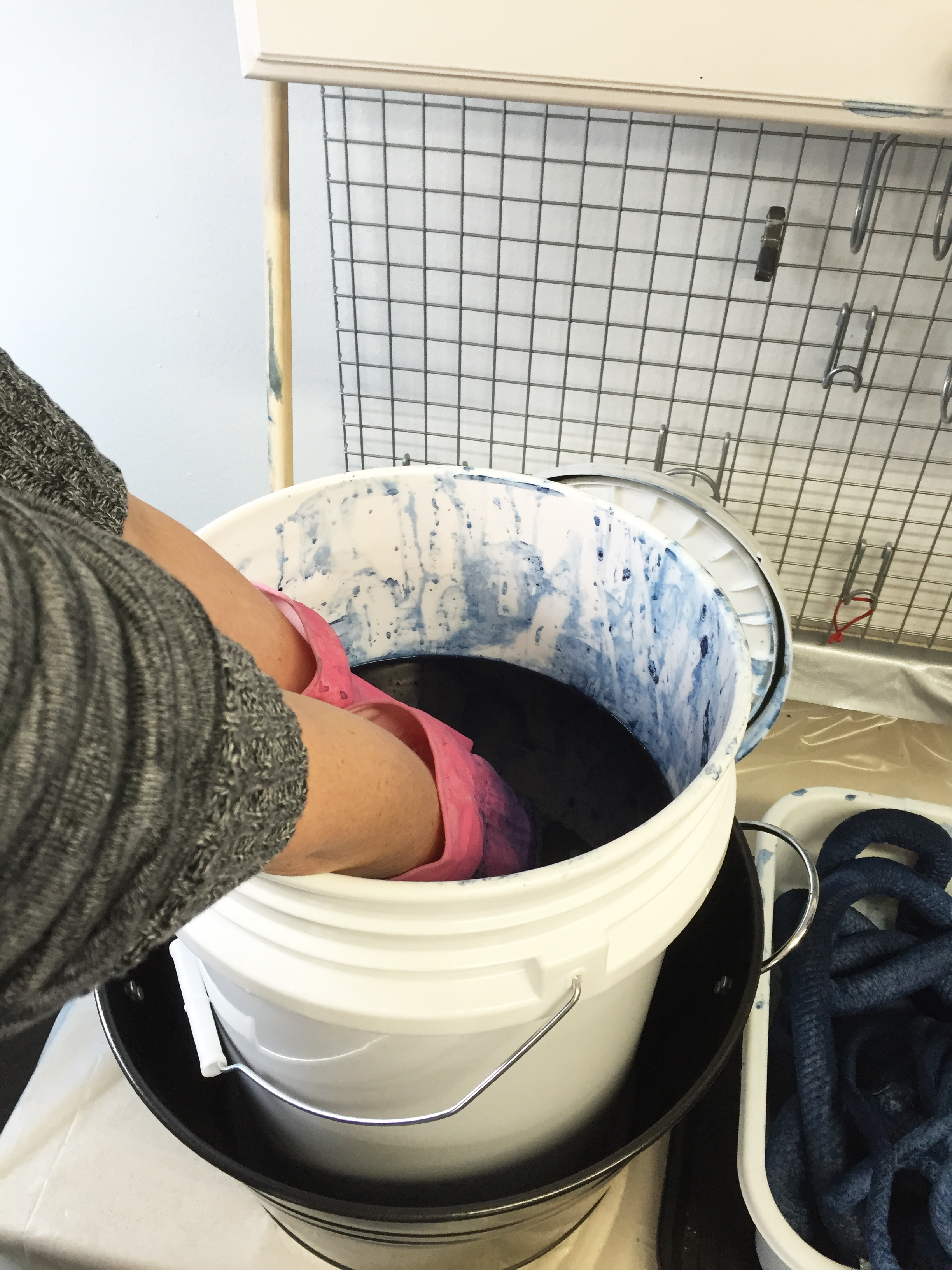 Melissa dips the tightly-scrunched piece of fabric down into the indigo dye.
