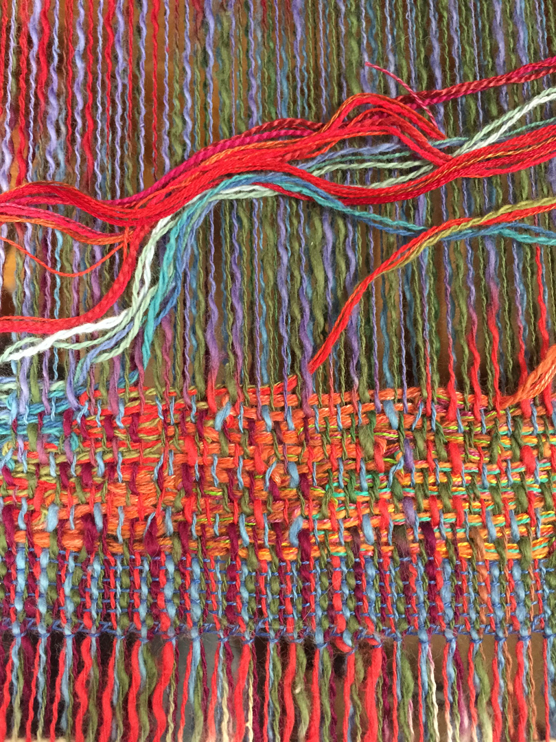 A close-up of the beginning of a weaving on the small loom.