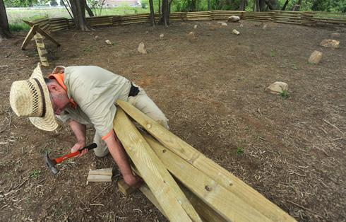 A member of the Campbell Guards (Sons of Confederate Veterans) assists in the construction of the cemetery fence.