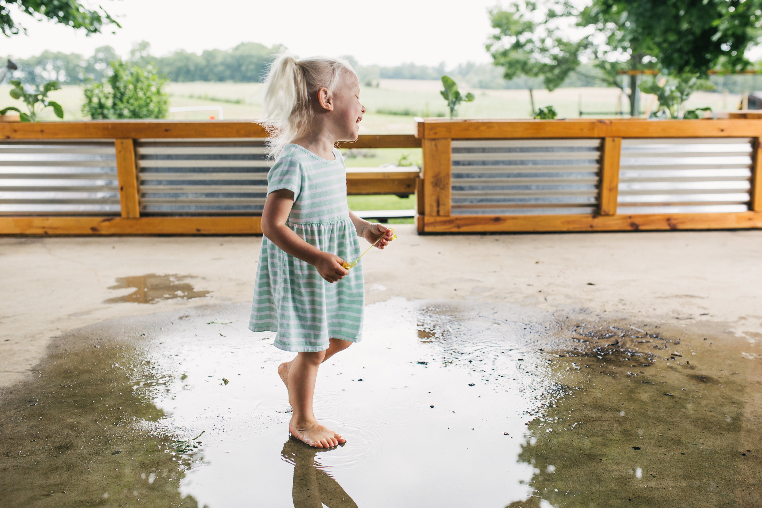 Family portrait of older sibling playing outside after a rainfall at their beautiful Maryland home.