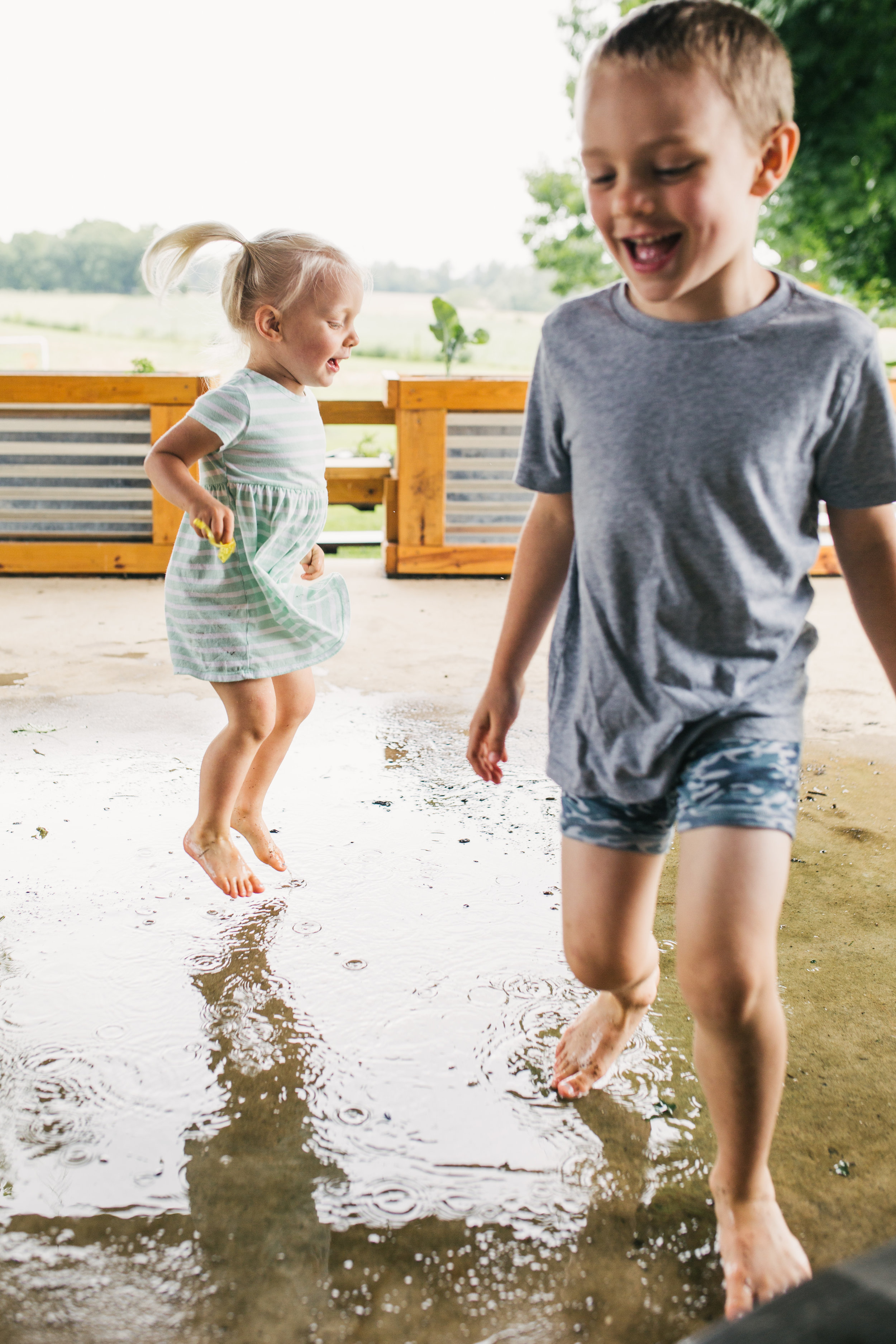 Family portrait of both older siblings playing in the puddles outside after a rainfall at their beautiful Maryland home.