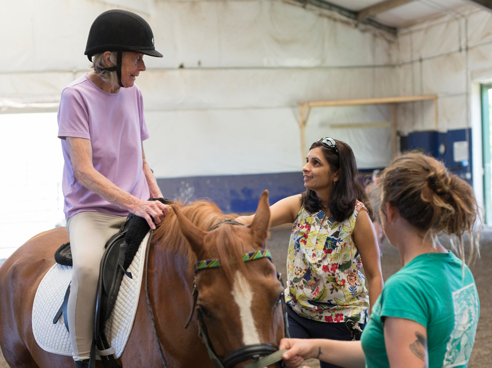 Penelope Maynard (left)is riding horses again thanks to help from Naseem Chatiwala, DPT, NCS, (center) a neuro specialist at Emerson's Center for Rehabilitative and Sports Therapies.