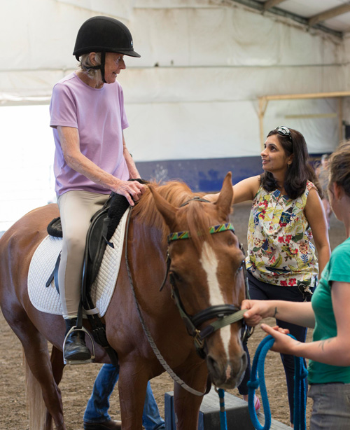 Naseem Chatiwala, PT, MS, DPT, NCS, (standing to right of the horse) is a clinical specialist in neurology and pediatrics at Emerson's Center for Rehabilitative and Sports Therapies. She helps patients overcome the challenges that result from strokes, vertigo, concussions and balance issues.