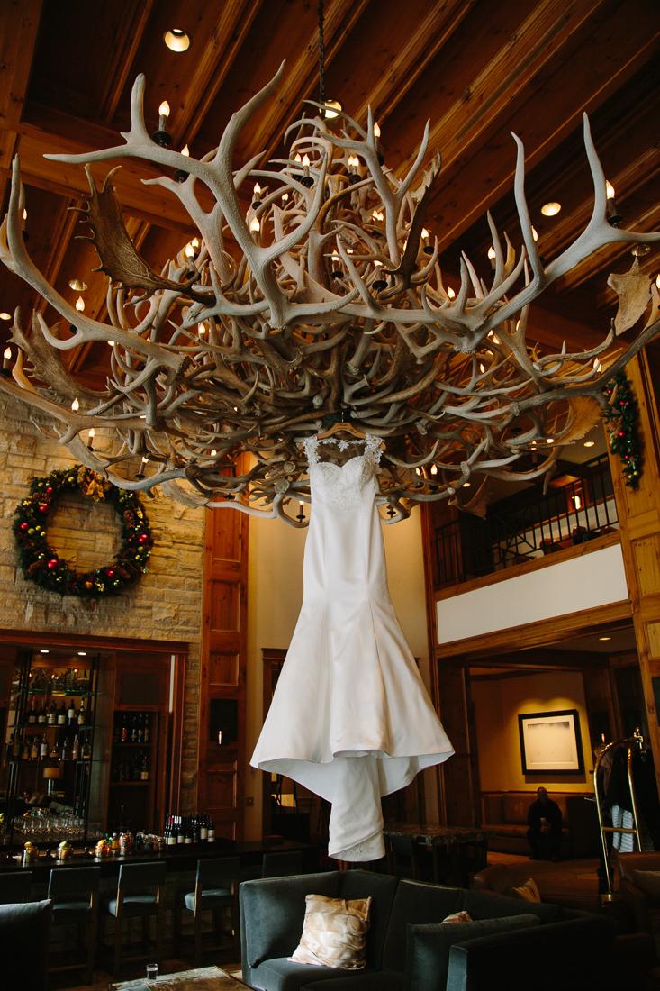 Cat Mayer Studio | www.catmayerstudio.com | Park Hyatt Beaver Creek Wedding | wedding dress hanging from antler chandelier