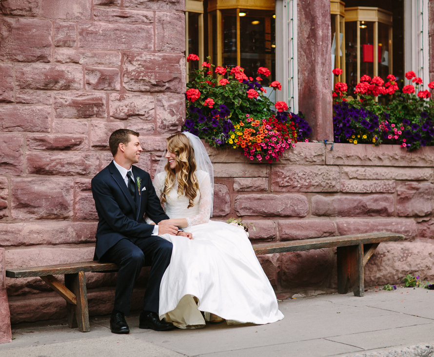 Bride and groom sitting on bench with flowers | Cat Mayer Studio | www.catmayerstudio.com