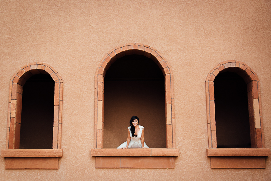 Bride Leans Over Stone Archway Windows | Cat Mayer Studio | www.catmayerstudio.com