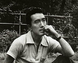 "Yukio Mishima, a gay Asian writer, actor, and filmmaker who helped shatter the glass ceiling for the LGBTQIA+ community, particularly in Asia through his controversial works. One such work was ""Confession of a Mask,"" a semi-autobiographical narrative about a gay man choosing to create a facade that will grant him societal acceptance."