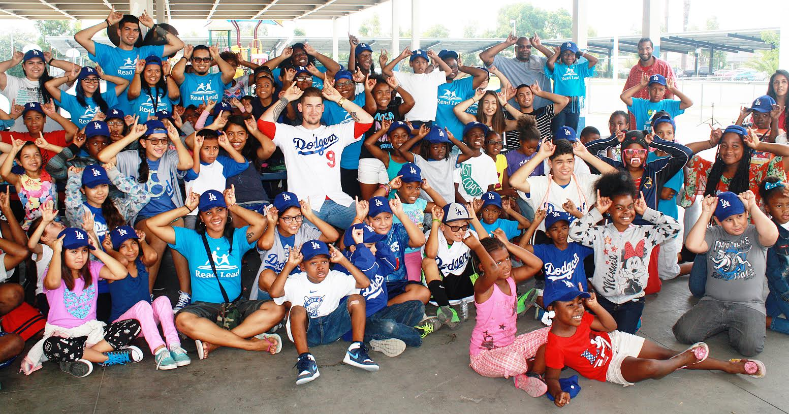 """More than 100 students at Lynwood Unified's Helen Keller Elementary School sit with Dodgers catcher Yasmani Grandal on Friday, July 31. The students are all posing with horns in honor of Grandal who is nicknamed """"Tasmanian Devil."""""""