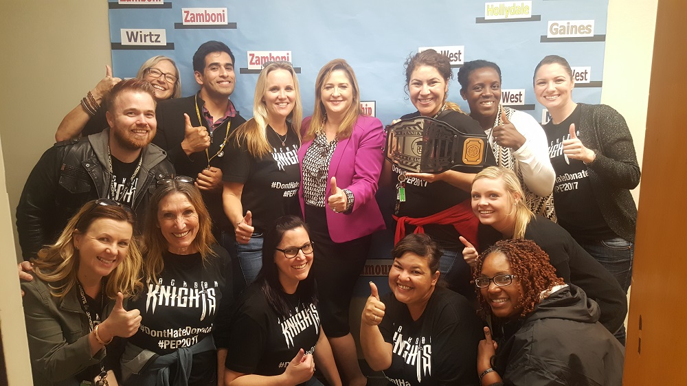 Jackson Middle School Principal Kelly Anderson, back middle left, celebrates with Paramount Superintendent Dr. Ruth Pérez, back middle right, and Jackson faculty and staff after winning the inaugural March Madness fundraiser, which raised over $95,000 for the Paramount Educational Partnership.
